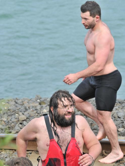 Dunedin personal trainer Alex Spenceley (right) walks along the Ravensbourne shore yesterday...