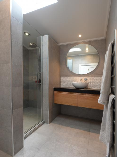 The bathrooms feature large grey tiles and oak vanities with granite tops. The white embossed...