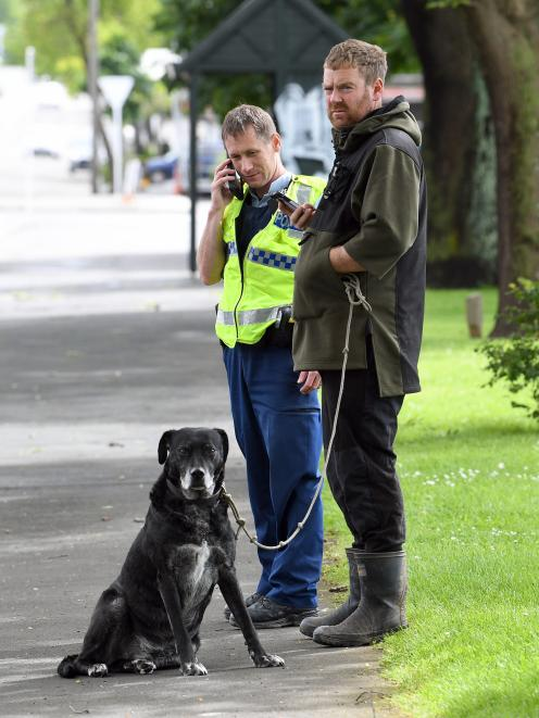 A bystander holds a dog who bit a man who stopped to help after its walker had a seizure, as...