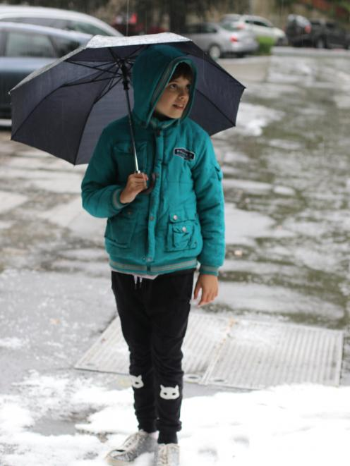 Orion Jacobs (10) shelters under an umbrella after a hailstorm in Dunedin today. Photo: Alison Jacobs