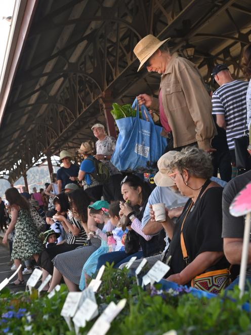 Shoppers seek shade under the platform canopy of the Dunedin Railway Station to enjoy food bought at the Otago Farmers Market on Saturday. Photo: Christine O'Connor
