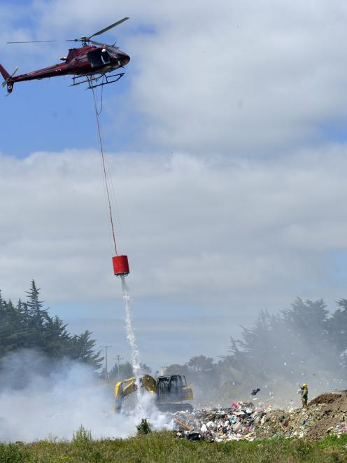 A helicopter with a monsoon bucket battles a blaze at the Mt Cooee landfill in Balclutha...