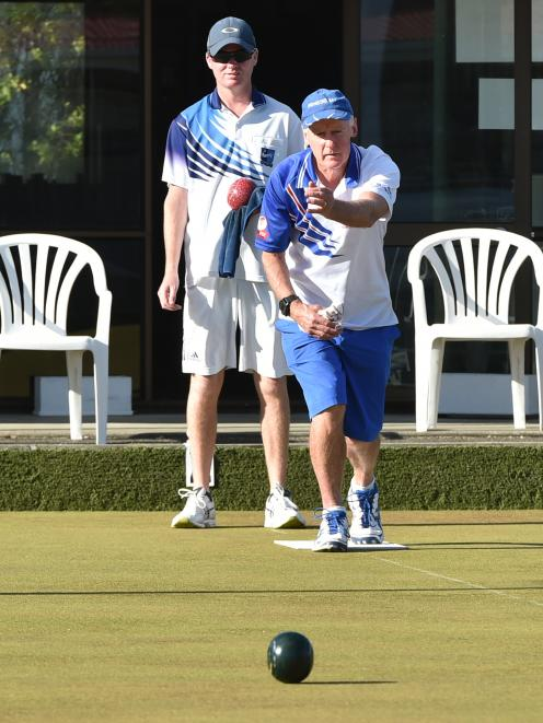 Paul King (front) watches his bowl while Brent McEwan looks on in the champion of champion singles final at Balmacewen Bowling Club on Tuesday night. Photo: Gregor Richardson