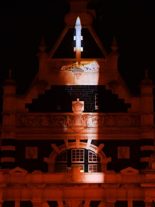As a tribute in the wake of last Friday's Christchurch mosque attacks, an image of a burning candle is projected on to the Dunedin Railway Station last night. Photo: Peter McIntosh
