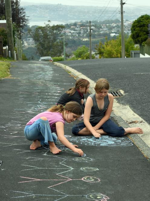 The Patterson sisters of Stratham St, in Brockville, (from left) Zoe (9), Erin (6) and Ada (11), have drawn a message to their neighbours whom they think were connected to the Christchurch tragedy. Stretching the well-walked route between houses of immigr