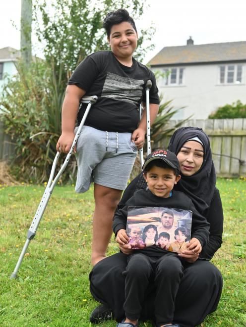Pine Hill former refugees Nisrine (36), Kasem (14) and Mohammad (5) Zarzar in their garden after the Christchurch mosque attacks with a picture of dead relatives including children Lamar, Samei, Basal and father Mohammad. Photo: Christine O'Connor