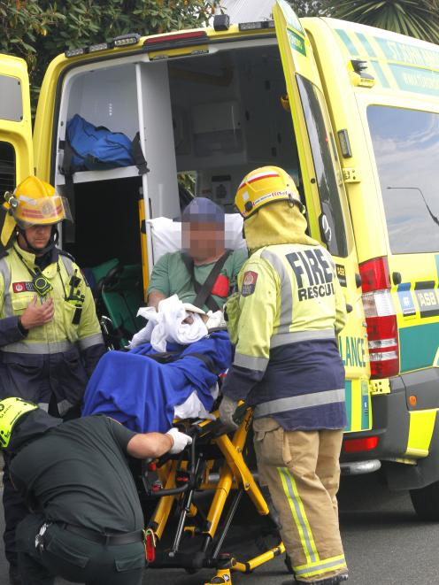 The man is loaded into an ambulance after he was rescued by firefighters. PHOTOS: GIORDANO STOLLEY