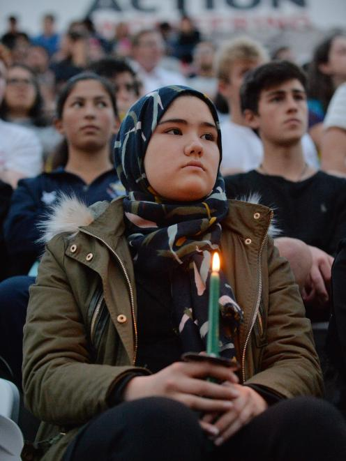A woman holds a candle in the crowd during last night's civic vigil at Forsyth Barr Stadium in...