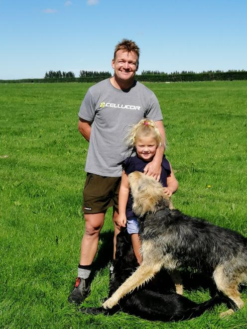 Eyrewell farmer Mike Smith hopes to pass his farm on to one of his daughters. He is pictured with his youngest daughter Millie (6) and dogs Ted and Blackie. Photo: Gina McKenzie