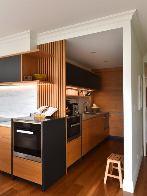 The scullery contains a pantry with a roll-up door, a steam oven and dishwasher.