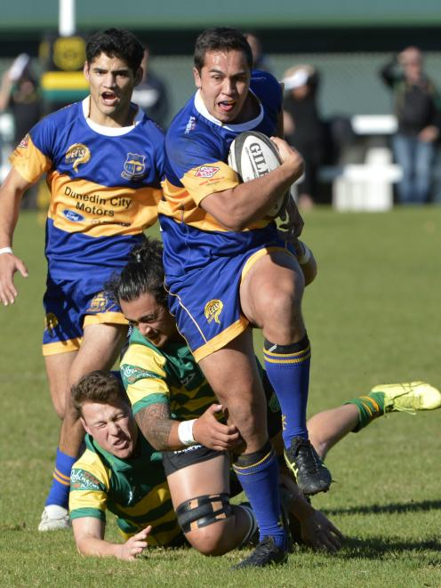 Taieri centre Matt Whaanga slips away from Green Island defenders Jesse Va'afusuaga and Finn...