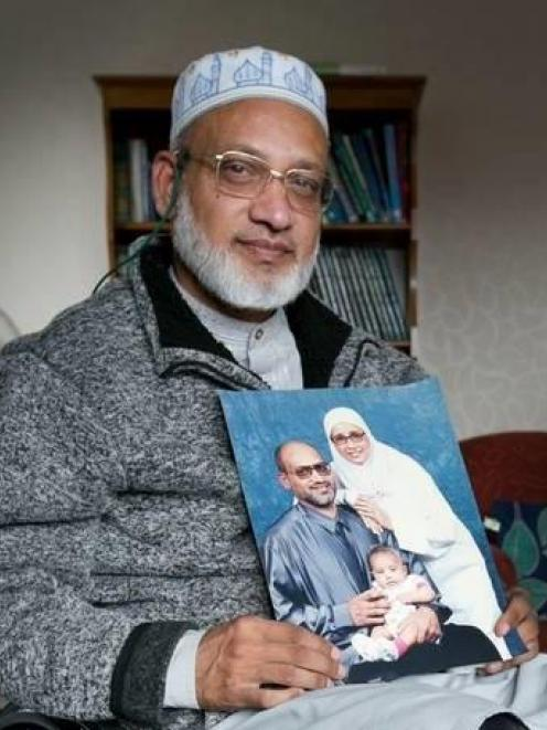 Farid Ahmed pictured holding a photograph of his family, including wife Husna Ahmed who was...