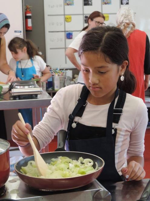 Erena Piho (9) stirs vegetables for the vegetable quiche.