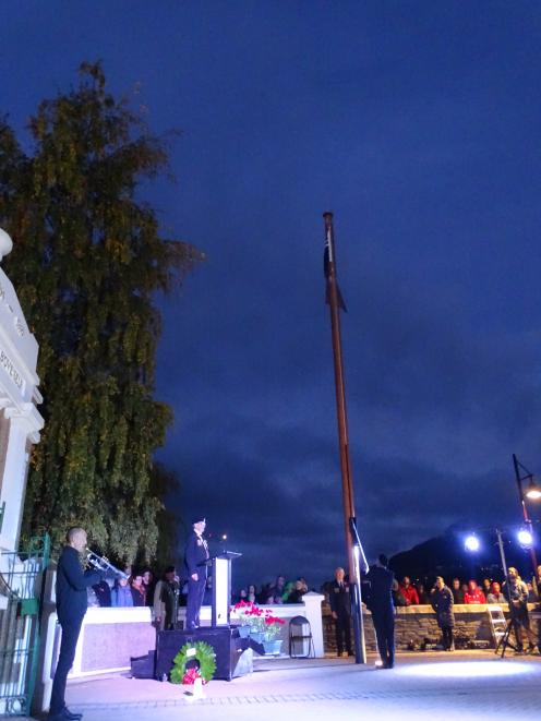 The New Zealand flag is raised during the dawn service in Queenstown this morning while bugler...