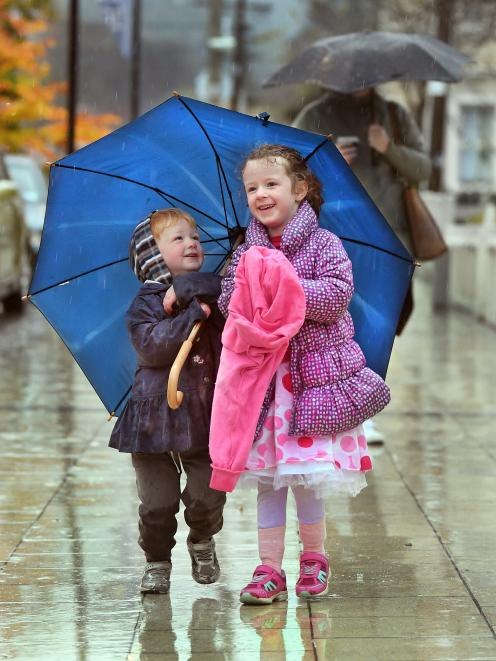 Siblings Eli (2) and Isobel (4) McConnell share an umbrella as they walk to daycare near the...