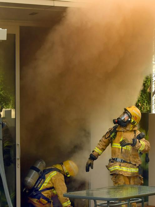 Firefighters crawl out of a smoke-filled house in Queenstown's Lancewood Lane yesterday morning....