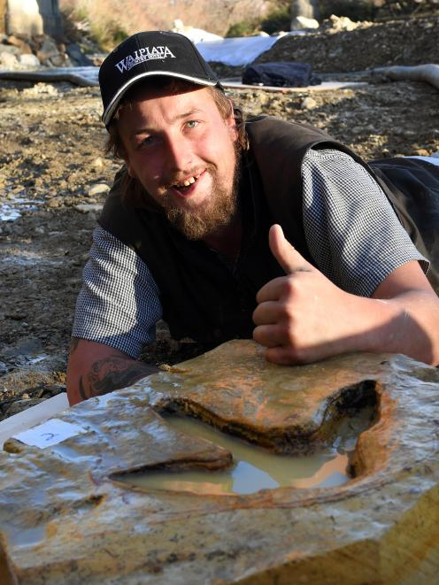 Ranfurly man Michael Johnston bonds yesterday with moa footprints he found in the Kyeburn River....