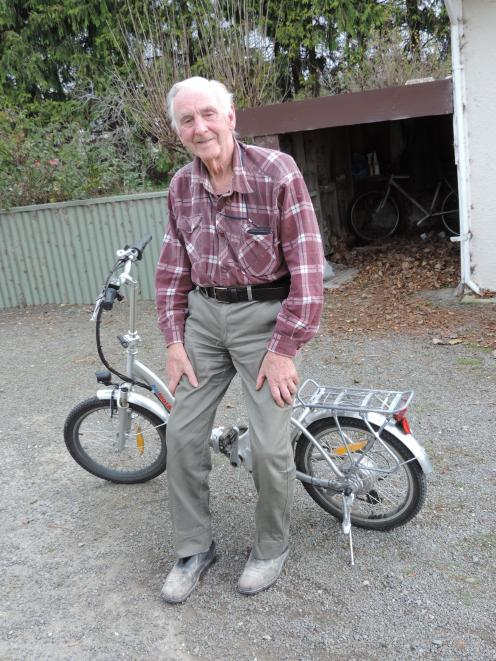 Jim Quested rides his e-bike to the hen houses. Photo: Sally Brooker