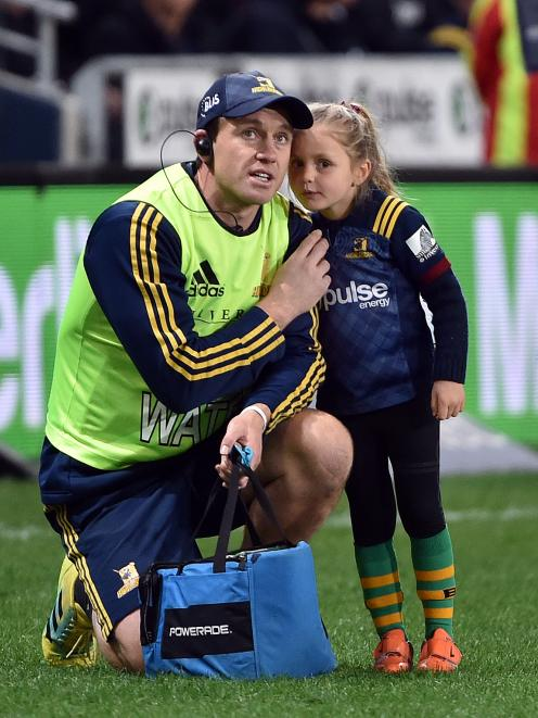 Highlander Ben Smith and his daughter, Annabelle, wait for the kicking tee to be brought out  at...