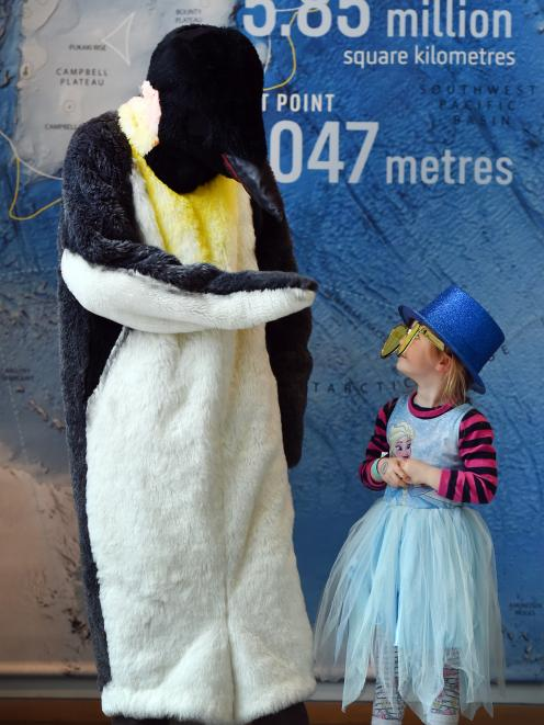 Nancy Hutchinson (4) chats to a penguin who was entertaining children at the exhibition.