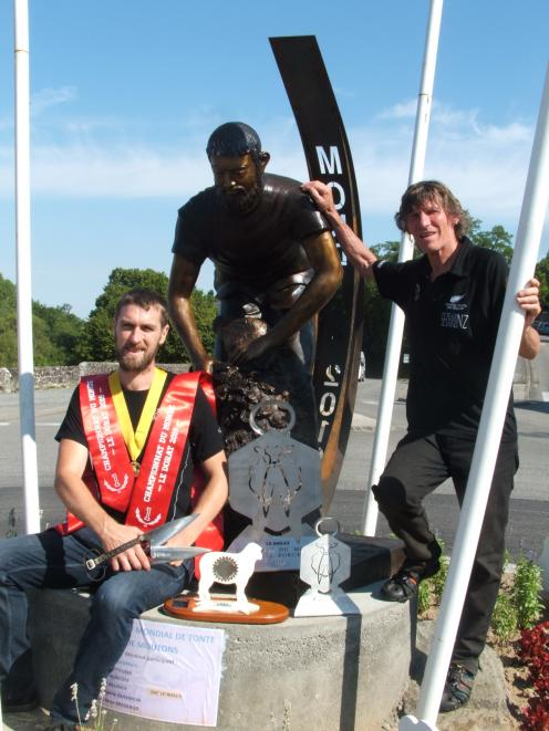 Allan Oldfield is pictured with his  world championship trophies next to a shearing statue in downtown Le Dorat, France, with his father and coach Phil Oldfield, who placed second in the 2017 world championships.Photo: Supplied