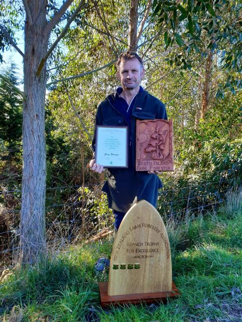 Gary Fleming proudly displays the South Island Farm Forester of the Year trophy and the branch trophy for excellence which he brought back from the New Zealand Farm Forestry Association conference in Rotorua this year. Photo: Supplied by Gary Fleming