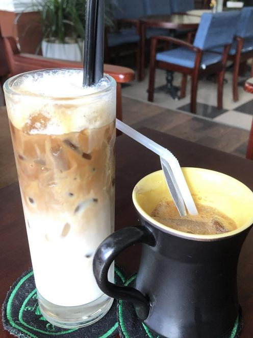 An iced ''white coffee'' made with milk and condensed milk alongside an iced ''milk coffee'' —...