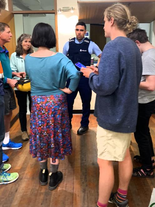 A police officer enters a school climate strike banner-painting session in Dunedin on Tuesday to question people. Photo: Supplied