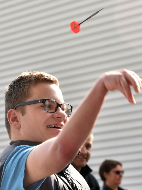 Hunter Edgecombe tries his hand at darts for the first time, during the Otago All Abilities Sports Day and Expo at Forsyth Barr Stadium yesterday. Photo: Peter McIntosh