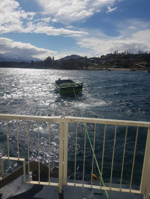 The houseboat Lady Pembroke is towed back to its moorings on Lake Wanaka by a jet-boat skippered...