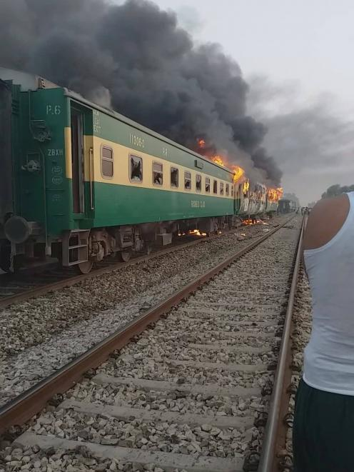 A train burns after a gas canister passengers were using to cook breakfast exploded, near the town of Rahim Yar Khan. Photo: Jawedasrar Siddiqui via Reuters