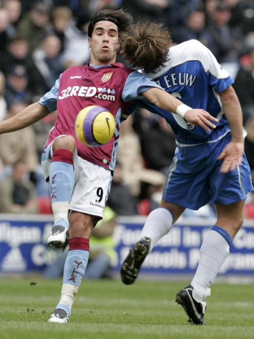 Aston Villa's Juan Pablo Angel is challenged by Wigan Athletic's Arjan De Zeeuw for the ball in this file photo from November 2006. Photo: Reuters