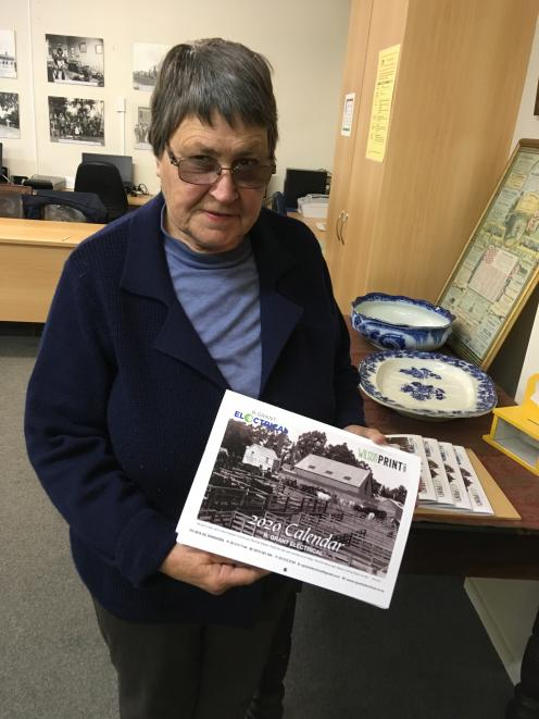 Rangiora Museum curator Ann Jelfs displays a 2020 calendar of old Rangiora photographs, which the museum is selling as a fundraiser.