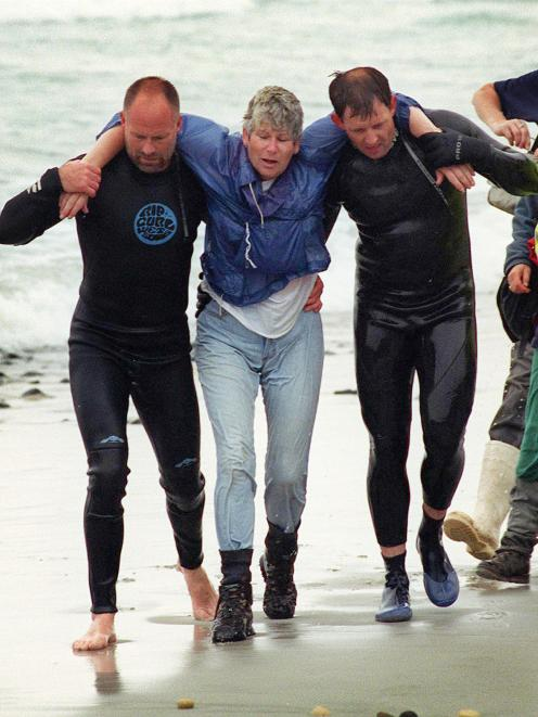 Margaret Dodds is helped to shore by rescuers Neil Price (left) and Senior Sergeant Brian Benn....