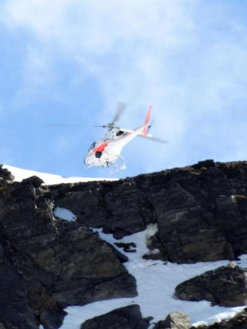 A helicopter flies over the site where two men died on the Remarkables yesterday. Photo: Guy Williams