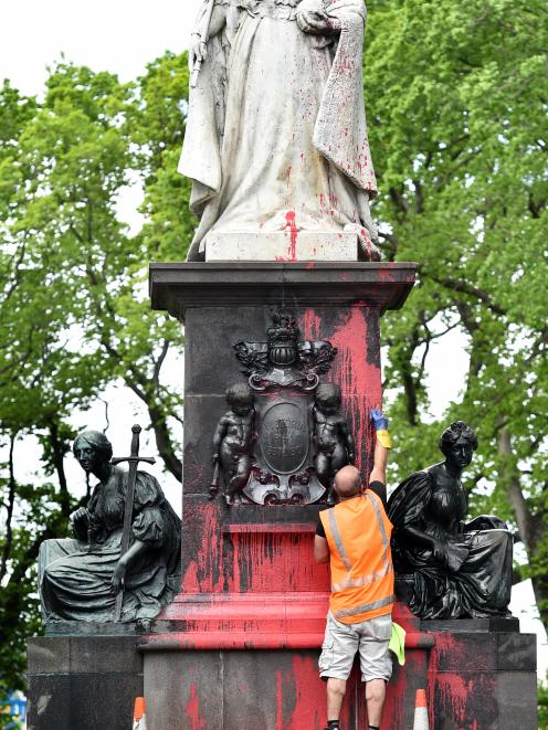 Roger Knauf, of Graffiti Doctor, starts the job of removing red paint from the historic Queen...