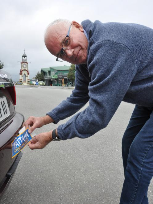 West Coast Electric Power Trust chairman Ian Hustwick shows the bumper stickers being distributed Coast-wide in support of the Waitaha hydro-electric scheme, thrown out by the Government. Photo: Hokitika Guardian