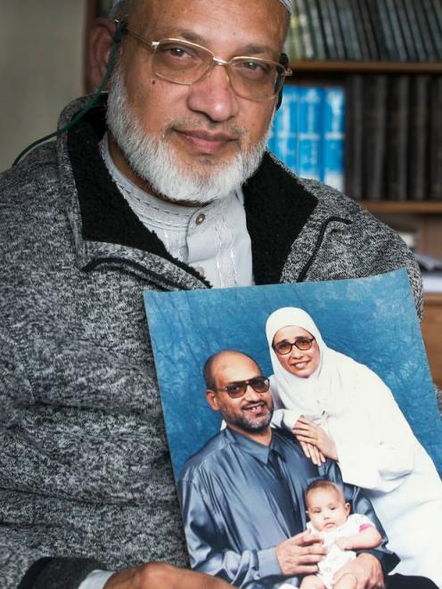 Farid Ahmed holds a photo of his wife Husna, who died saving lives when a gunman opened fire in...