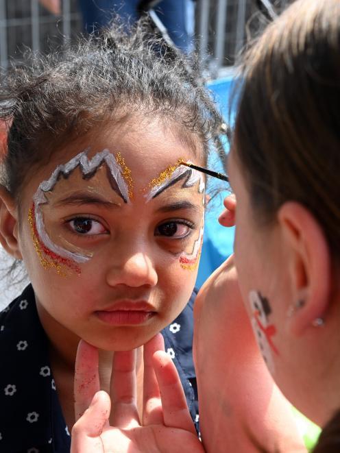 Vaiola Kafa Tangimana (4) has her face painted as an angel by volunteer Maya Threlfall at...