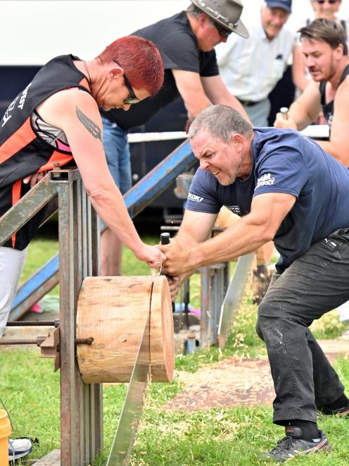 Karen Richards works as a wedger as Adam Findlay, of Omakau, competes in the single sawing event.