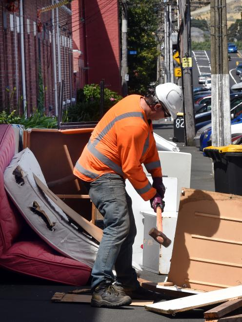 A contractor breaks up discarded furniture before removing it on Dundas St, in Dunedin's student quarter, yesterday. Photo: Stephen Jaquiery