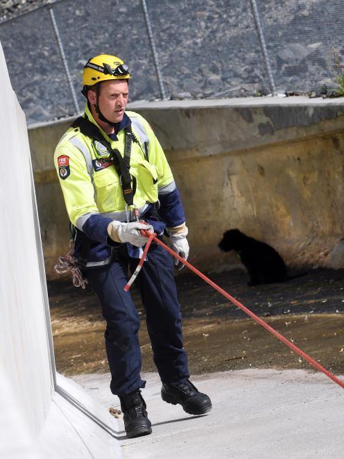 Willowbank firefighter Matt Burke abseils down the steep Ross Creek Reservoir dam's outlet chute,...