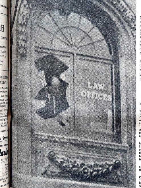 Detective Sergeant E.R. Tyson examines the window that was shattered by the blast in James Ward's office. Photo: Staff Photographer
