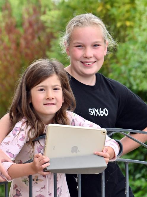 Charlotte (6) and Brooke Reddington (10) are finding there are pros and cons in doing school work...