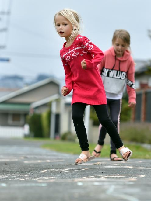 Lexi (front, 6), and Lara Lowe (8) try out a hopscotch game on Bayview Rd. Photo: Peter McIntosh