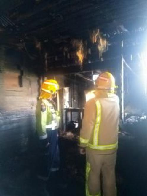 Firefighters inspect the smoke and fire-damaged home. Photo: Supplied