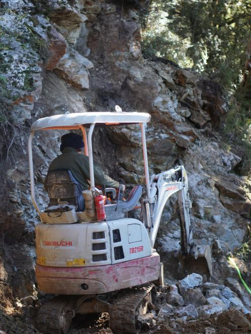 Diggers cut into the cliff face to make a safe path.