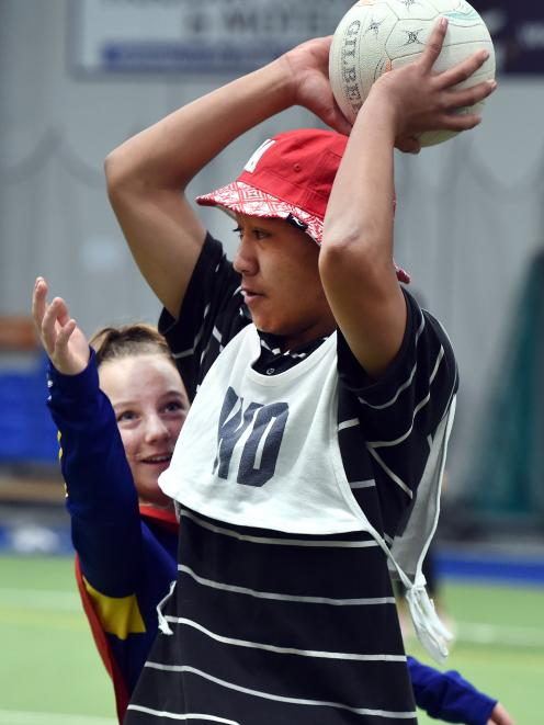 Taufa Makanesi (13) goes to pass the ball despite the attentions of defender Melody Buckby (12).