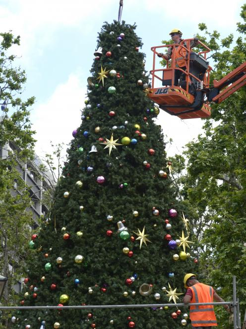 Contractors assemble the 12m Octagon Christmas tree yesterday morning which will be lit in the annual tree lighting ceremony on Friday. Photo: Gerard O'Brien