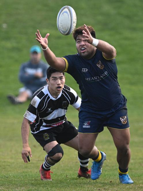 Dunedin hooker Naryan Strickland comes under pressure from Southern wing Riku Kitahara as he...